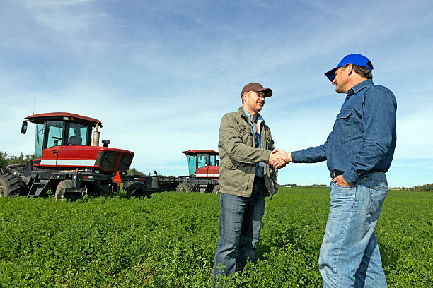 A royalty free image from the farming industry of two farmers shaking hands.